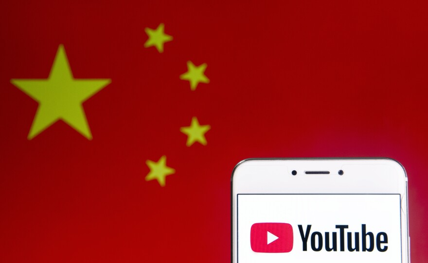 An illustration of the video-sharing website Youtube logo and an Android mobile device with People's Republic of China flag in the background.