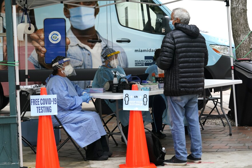 """Healthcare workers sit at a white foldout table underneath a white tent. The workers wear medical gowns, face shields, and face masks. On the table are various medical supplies such as hand sanitizer and face masks. A man in jeans, a puffy jacket, and a surgical mask stands in front of the table. Two orange traffic cones are set up in front of the tent. A sign on one cone reads, """"Free COVID-19 Testing."""" The other cone has a sign that reads, """"Six feet. Keep your distance."""" Behind the healthcare workers is a large vehicle with the words, """"Miami-Dade County,"""" printed on it."""