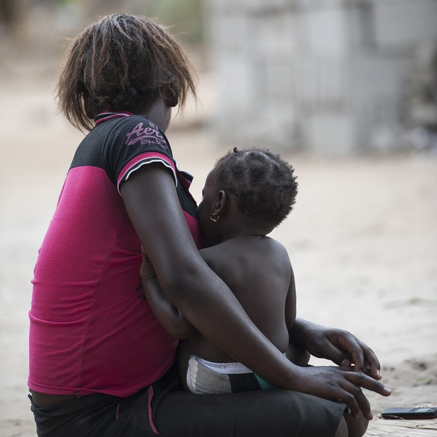 In this November 2015 photo, A 17-year-old mother sits with her baby in the Inhassune village, in southern Mozambique. In Mozambique there are no laws preventing child marriages and existing child protection laws offer loopholes. If a community decides that a girl is to be married in a traditional ceremony, with or without her consent, lawmakers are powerless to intervene.