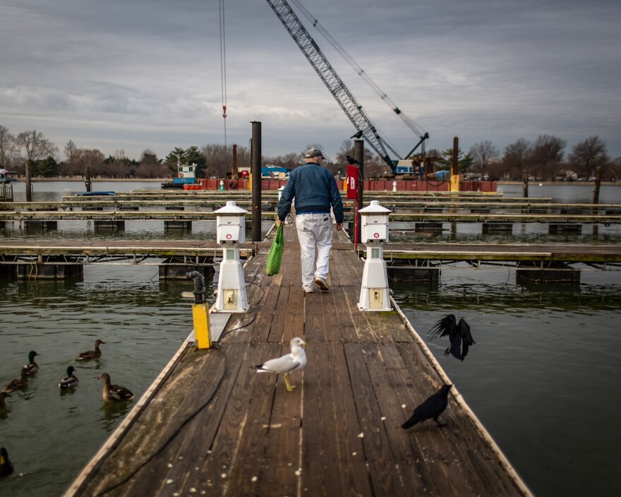 Thiel feeds the birds on the last day that Gangplank residents had access to the marina's wooden docks.