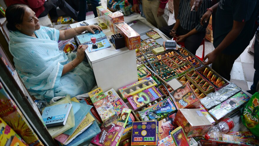 An Indian shopkeeper sits at her firecracker shop in New Delhi on Oct. 9, as India's top court ordered a temporary ban on the sale of firecrackers in New Delhi ahead of the Diwali festival.
