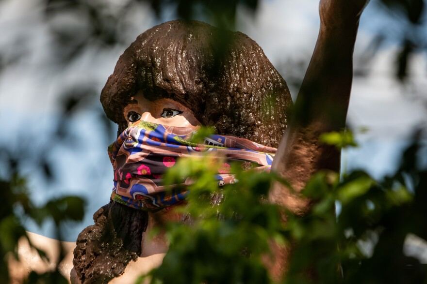 A face covering is placed over a statue at Taco Xpress in South Austin during the coronavirus pandemic.