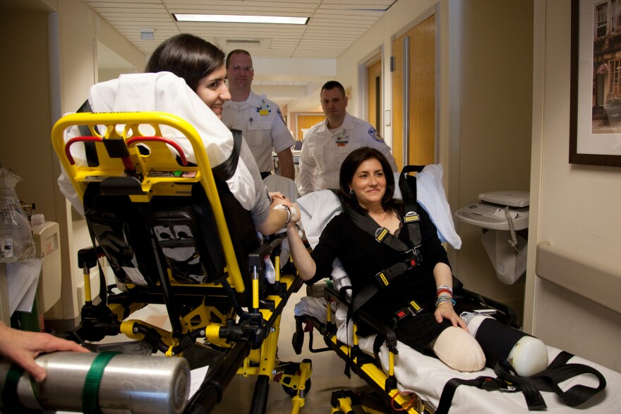 Celeste Corcoran (right) and her daughter Sydney Corcoran are transported to Spaulding Rehabilitation Hospital from Boston Medical Center on April 28. Sydney, who nearly bled to death after being struck by shrapnel in her thigh, is expected to recover most if not all function. Celeste required amputations of both legs. Doctors say the next phase of her recovery will be a holding pattern.