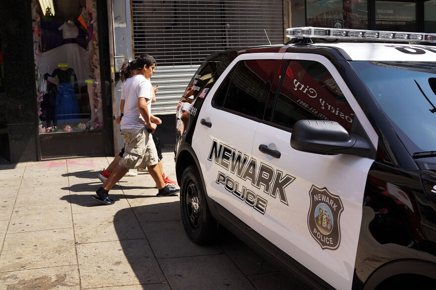 People walk by a police car in downtown Newark, N.J., in May 2014.