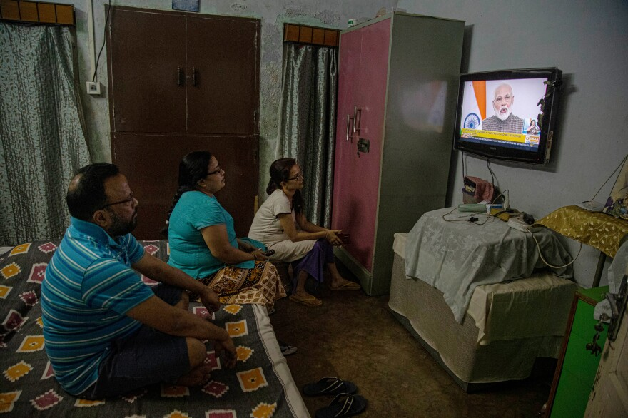 A family watches Prime Minister Narendra Modi announcing plans for a total lockdown to prevent the spread of COVID-19.