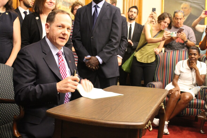 St. Louis Mayor Francis Slay signs an increase in the St. Louis minimum wage into law on Aug. 28, 2015.