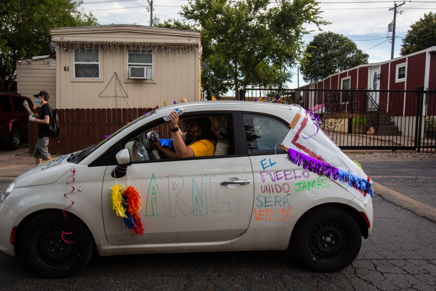 People parade through the mobile home park in decorated cars.
