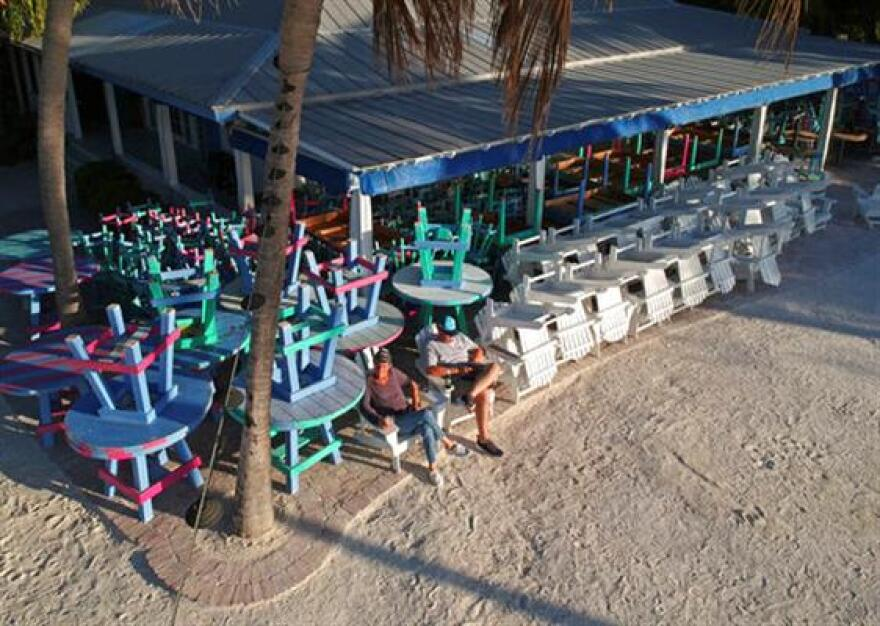 Employees of the Morada Bay Cafe in Islamorada, Fla., sit on chairs usually occupied by visitors