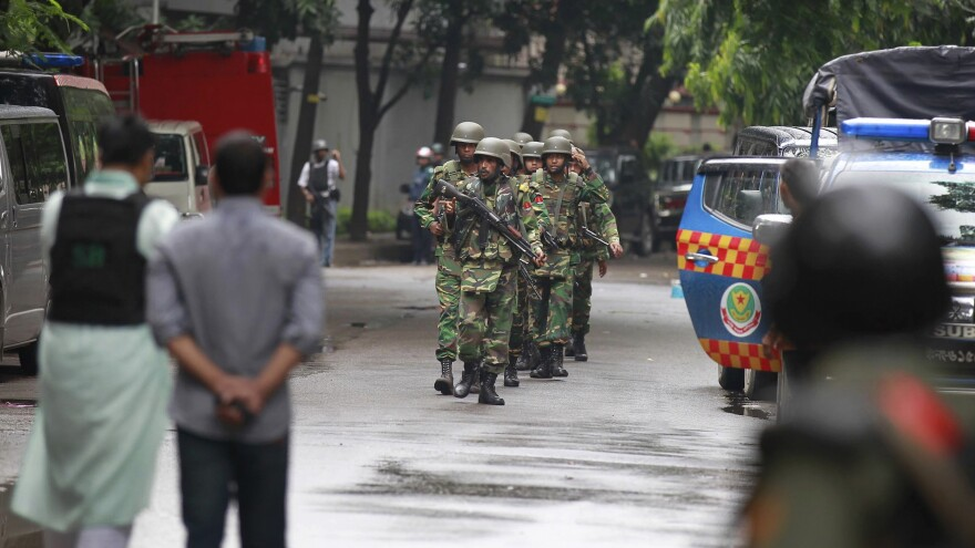 Bangladeshi soldiers come out of an area of Dhaka, Bangladesh, housing a restaurant popular with foreigners early Saturday, hours after heavily armed militants attacked it on Friday night and took dozens of hostages. Bangladeshi authorities stormed the cafe early on Saturday.