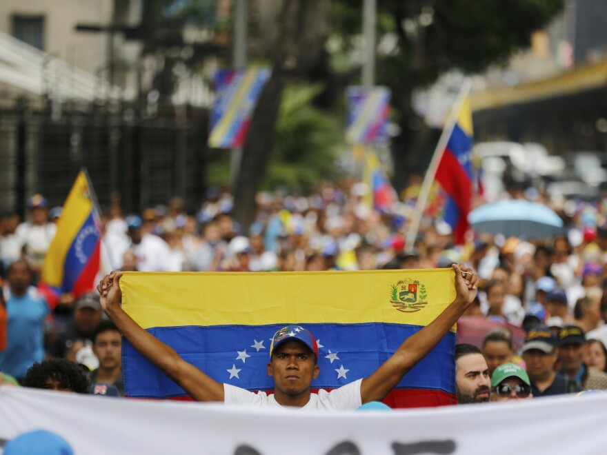 An opposition member holds a Venezuelan national flag during a protest against Maduro in Caracas on Wednesday.