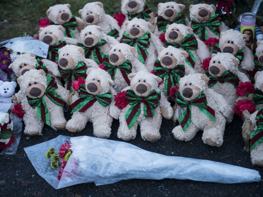 Stuffed animals and flowers at a makeshift memorial near the entrance to the grounds of Sandy Hook Elementary School.