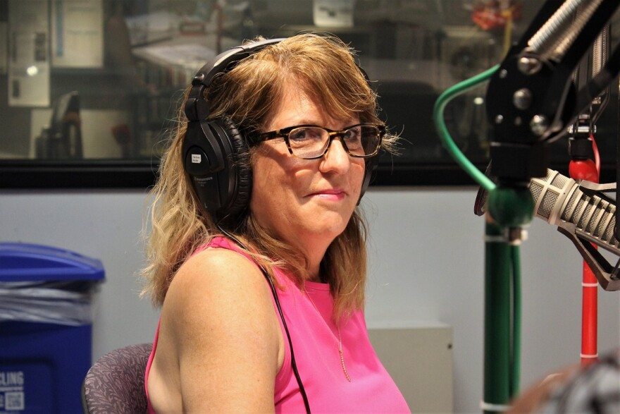 Sharon Liese seated in front of a radio microphone in the KCUR studio.