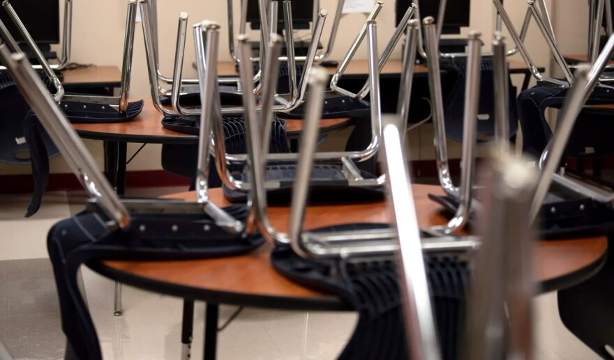 In an empty school room, desk chairs are set upside down on the desks.