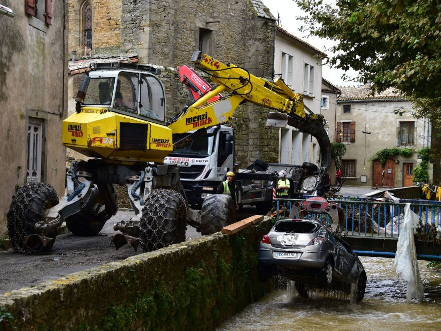 An excavator pulls a car from a river in Villegailhenc. It was just one of many vehicles that were damaged in flash floods overnight in southwest France.