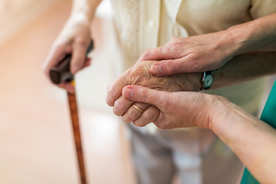 Nurse consoling her elderly patient by holding her hands.