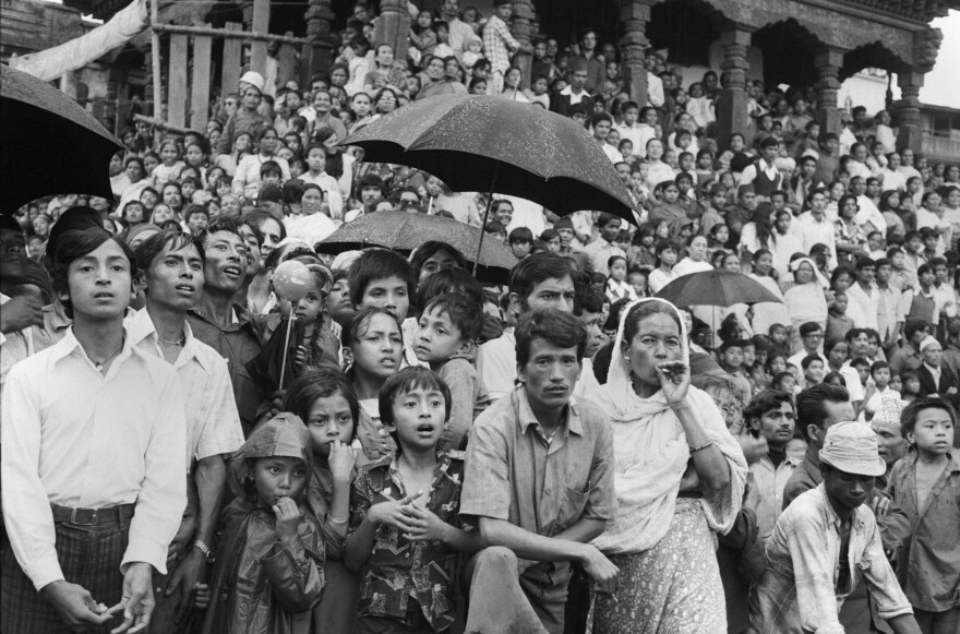 """A monsoon rain doesn't deter the devout from witnessing a chariot ride by a young girl worshipped as a living goddess known as Kumari — derived from the word for """"virgin."""" Kathmandu, 1975."""