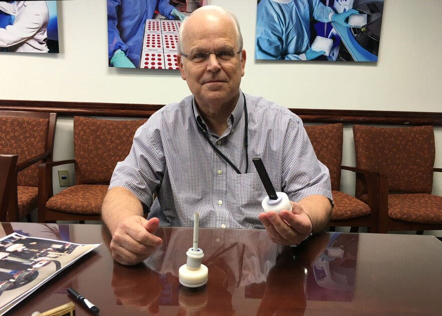 CDC's Dr. Jim Pirkle holds an e-cigarette attached to test base.