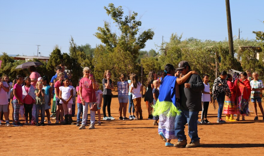 Photo of a man and woman dancing together in the middle of a red dirt corral as children look on.