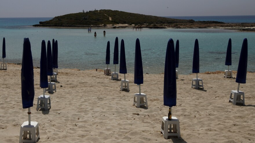 """Hoping to draw tourists to Cyprus this summer, officials cite the """"open-air lifestyle, abundance of personal space"""" and clean air. Here, rows of beach umbrellas await visitors on a nearly empty stretch of Nissi beach at the seaside resort of Ayia Napa earlier this month."""