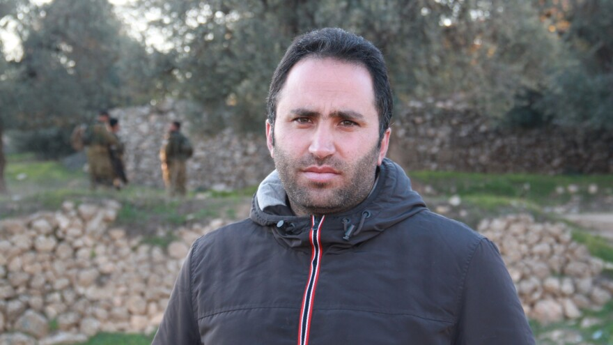 Palestinian activist Issa Amro advocates nonviolence in the West Bank city of Hebron. He recently talked a teenage girl out of an attack, but acknowledges it can be difficult to persuade young Palestinians to his position. In the background, Israeli soldiers patrol an olive tree grove next to his home, which the army has declared off-limits to non-residents.