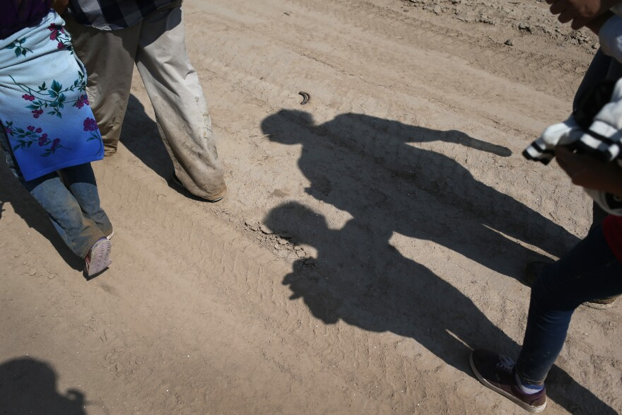 Central American immigrant families walk after crossing from Mexico into the United States to seek asylum in Texas.