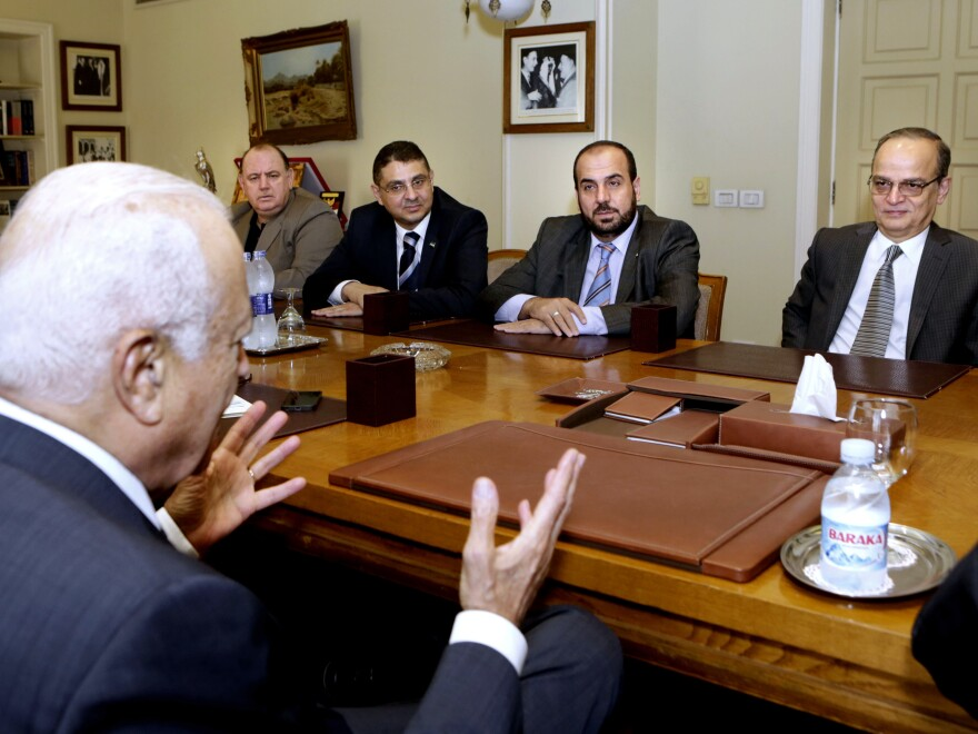 Arab League Secretary-General Nabil Elaraby (foreground) speaks to the head of the Syrian Coalition (second from right) during a meeting in Cairo, Egypt, on Monday. Elaraby is urging the league's members to confront Islamic State extremists.