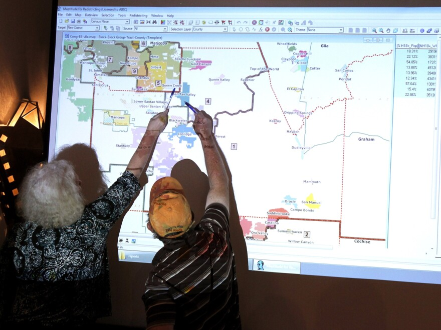 Attorney Mary O'Grady, left, speaks with Stephen Miller, a Casa Grande city council member, as they point to a possible map outlining the new congressional landscape during a Arizona Independent Redistricting Commission meeting in 2011.