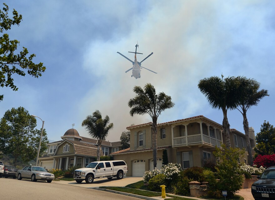 A fire fighting helicopter comes in to make a water drop behind some home threatened by a wildfire on Thursday in Newbury Park, California.