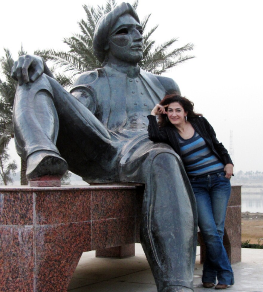 After a 20-year absence, Aseel Albanna returned to her native Iraq and found a very different country. Here, she poses with the statue of King Shahryar, a character in <em>The Thousand and One Nights</em>, near the Tigris River in Baghdad.