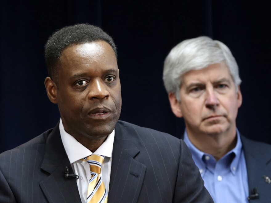Detroit emergency manager Kevyn Orr (left) speaks at a news conference in Detroit as Michigan Gov. Rick Snyder, who appointed Orr, listens. Orr's plan for the city to emerge from bankruptcy was approved by a federal judge today.