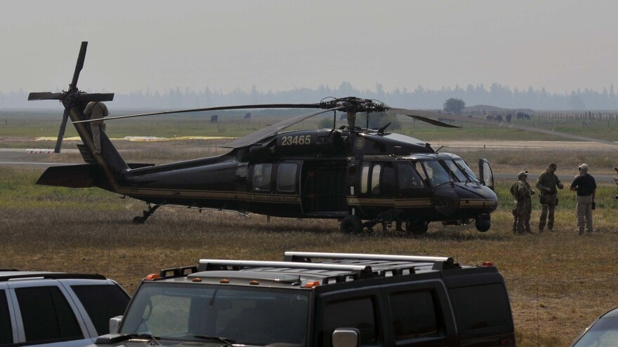 Authorities wait near a blackhawk helicopter at the Cascade Airport in Cascade, Idaho, on Saturday as they comb Idaho's Frank Church River of No Return Wilderness.