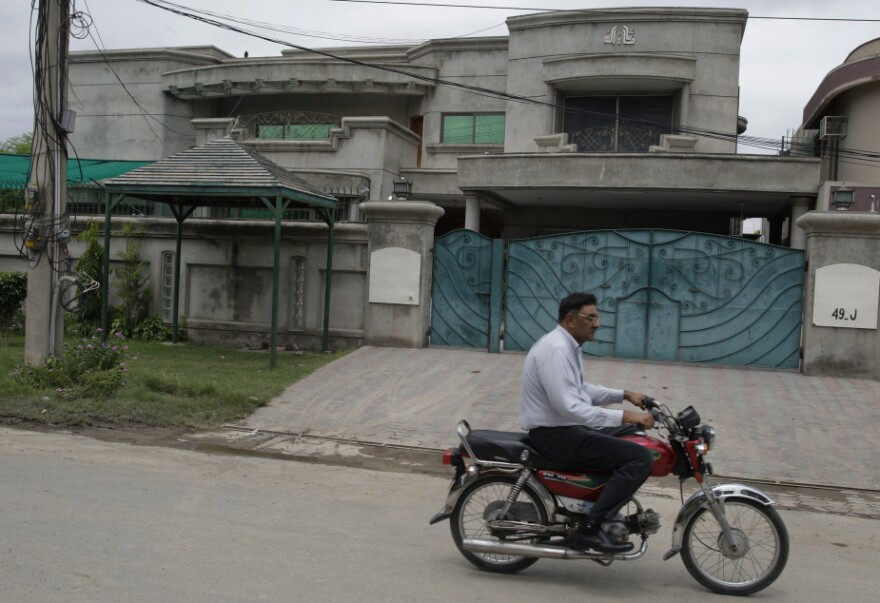 A man rides past the house of kidnapped American aid expert Warren Weinstein in Lahore, Pakistan. Weinstein was kidnapped more than two months ago; so far no demands have been made for his return.