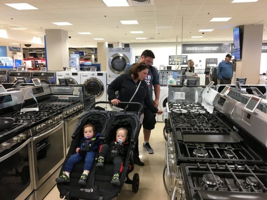 Carla and Jeremy Lang push their twin 18-month-old sons in a stroller while looking at ovens and stoves at a Sears northwest of Chicago in 2017.