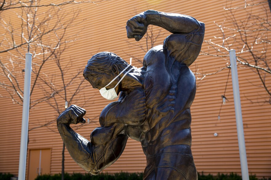 A statue of Arnold Schwarzenegger wears a face mask in downtown Columbus.