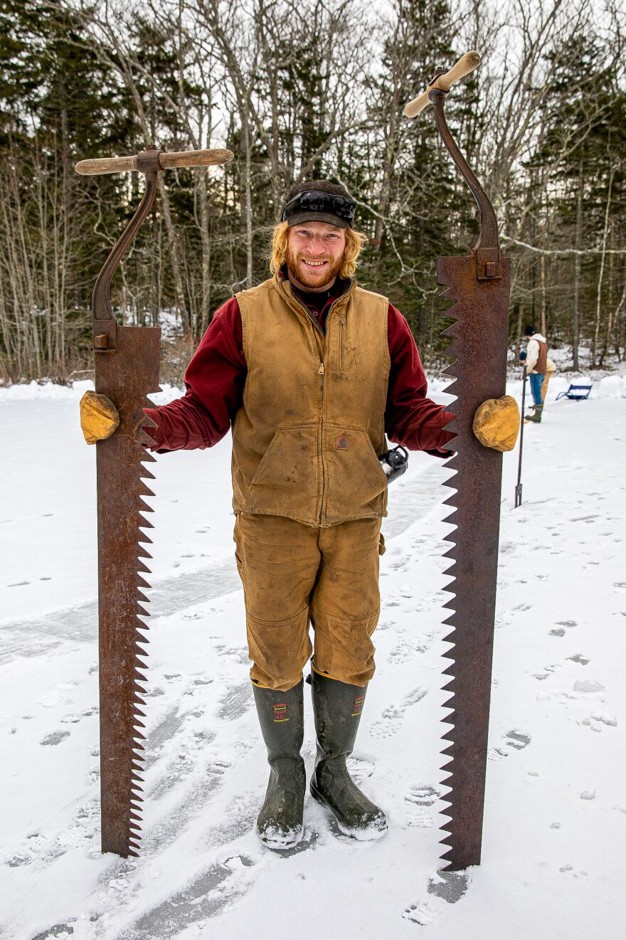 Zachary Plummer holds two pond ice cutting saws.