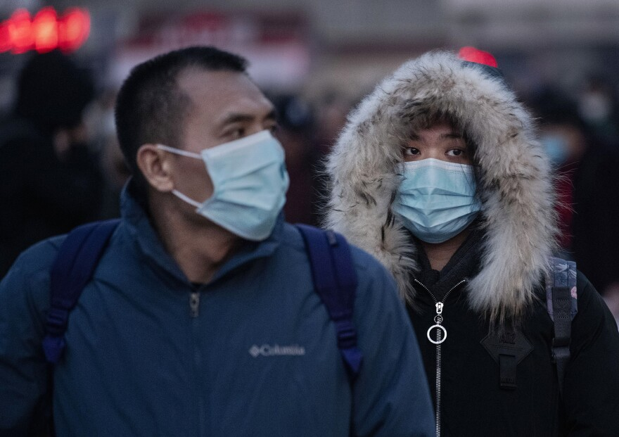 Chinese travelers wear protective face masks to protect themselves from the new coronavirus at the Beijing Railway Station on Jan. 21, 2020, in Beijing, China. COVID-19 was first identified in Wuhan, China, in December 2019, and since then has quickly spread worldwide.