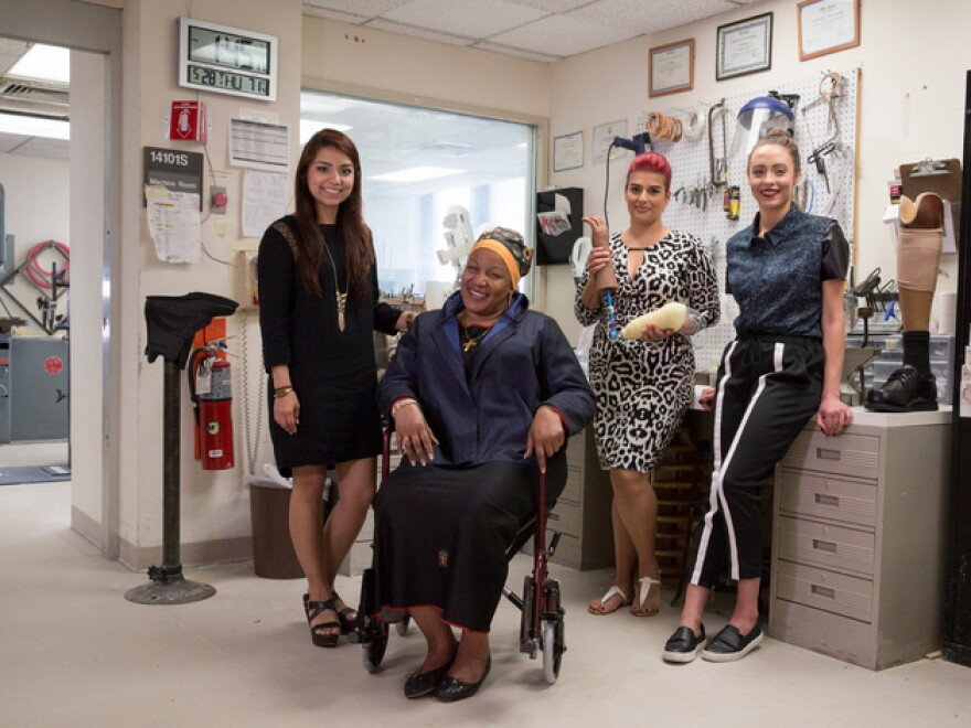 Fashion Institute of Technology students Erika Morales (left) and Nas Rivera (third from left) worked with Air Force veteran Anna Smith (seated) and fit model Samantha Poulis to design and produce clothes for people with disabilities, including amputees and people who use a wheelchair.