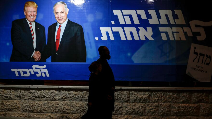 "Pedestrians pass an Israeli election billboard for Prime Minister Benjamin Netanyahu's Likud Party, which depicts him shaking hands with President Trump. The caption written in Hebrew reads: ""Netanyahu, in another league."""