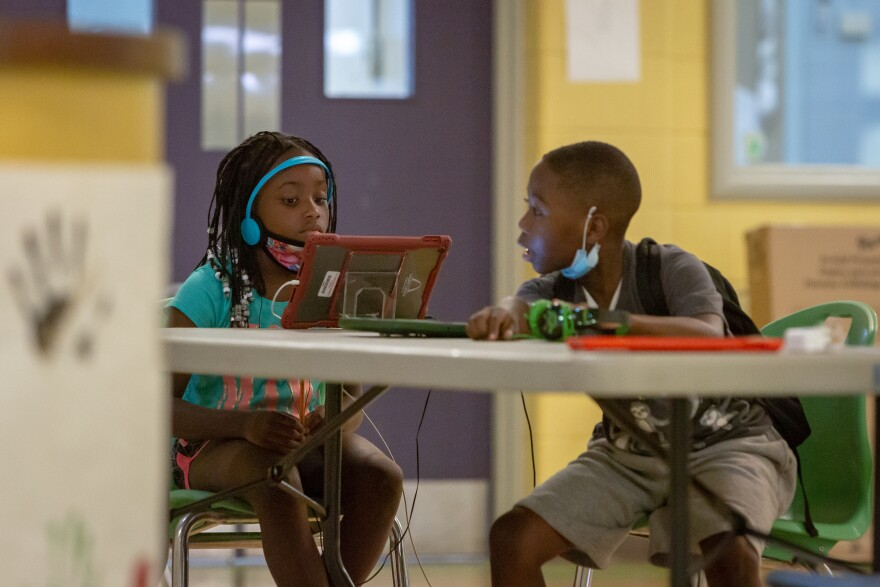 Two children work on remote lessons at the Gene Slay's Girls and Boys Club in Soulard on Sept. 9, 2020. The club opened an all-day learning center for up to 54 children to do schoolwork while schools remain closed during the coronavirus pandemic.