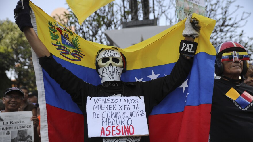 "An anti-government protester on Saturday in Caracas wears a sign that reads, ""Venezuelans die for lack of medicines. Maduro is an assassin."" Momentum is growing for opposition leader Juan Guaidó, who has called supporters into the streets."