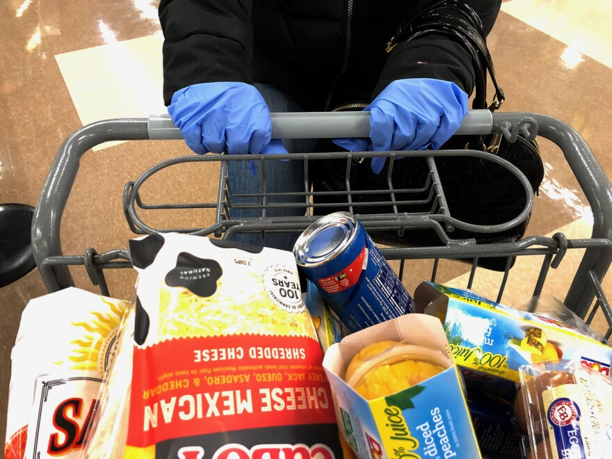 Many customers wear gloves while shopping at a supermarket in Saugus, Massachusetts on March 13, 2020. (Joseph Prezioso/AFP via Getty Images)