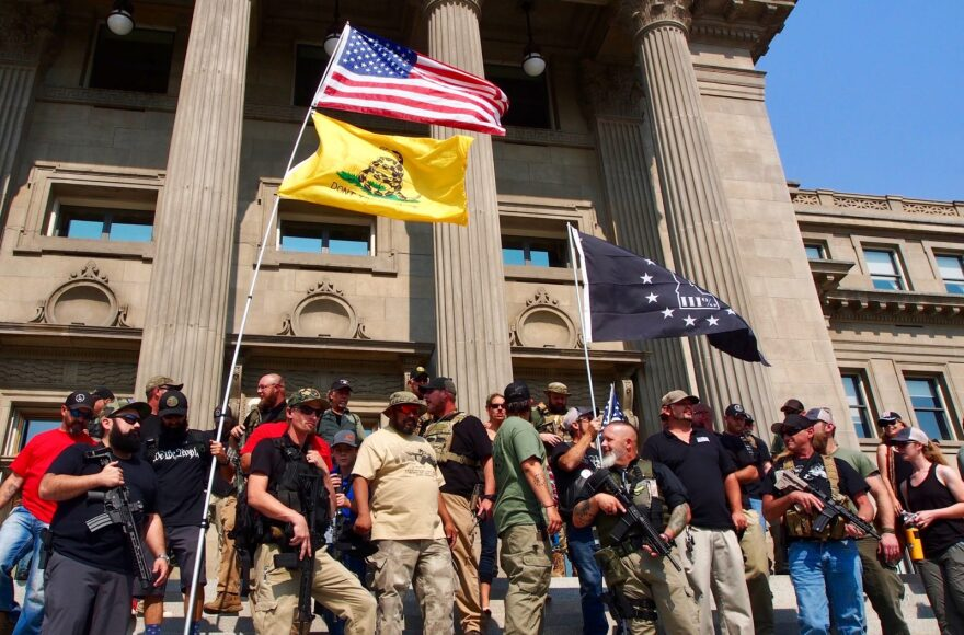 """Gun rights activists, including members of the anti-government group The Three Percenters, stand on the steps of the Idaho State Capitol during a gun rights rally in September 2018. Three Percenters have been part of an effort by """"no compromise"""" gun rights activists to make it harder to prosecute those who claim self-defense in shootings under proposed """"stand your ground"""" bills."""