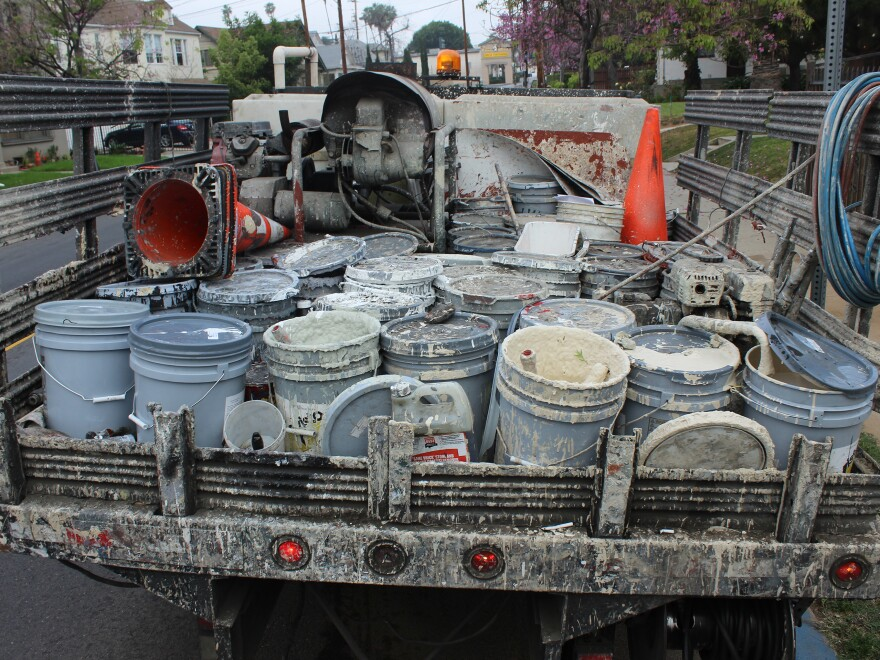Larry Bender's truck is equipped with an airless paint sprayer and high-pressure washer. The bed of his truck is like his paint palette, piled with five-gallon paint buckets, paint brushes and rollers.