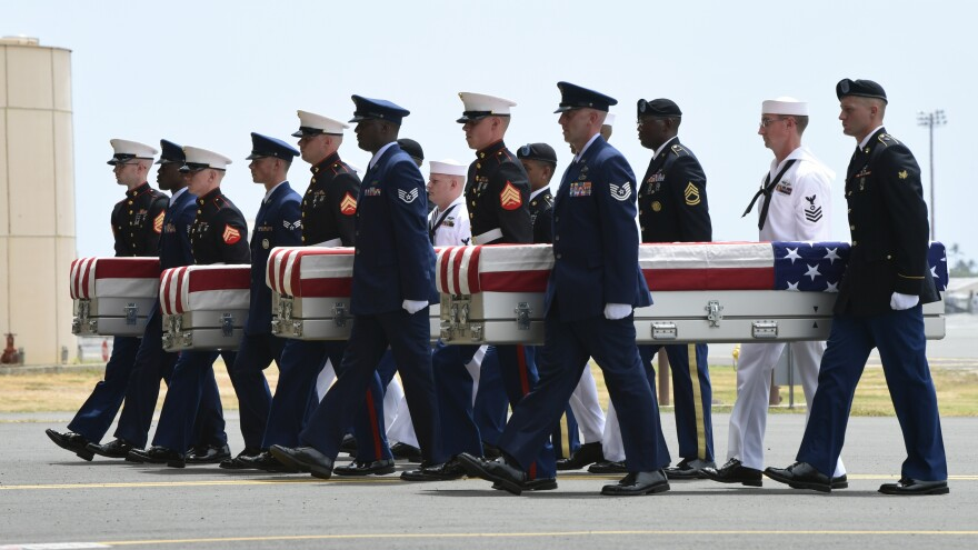 Military members carry transfer cases from a C-17 at a ceremony marking the arrival of the remains believed to be of American service members who fell in the Korean War at Joint Base Pearl Harbor-Hickam in Hawaii, on Wednesday.