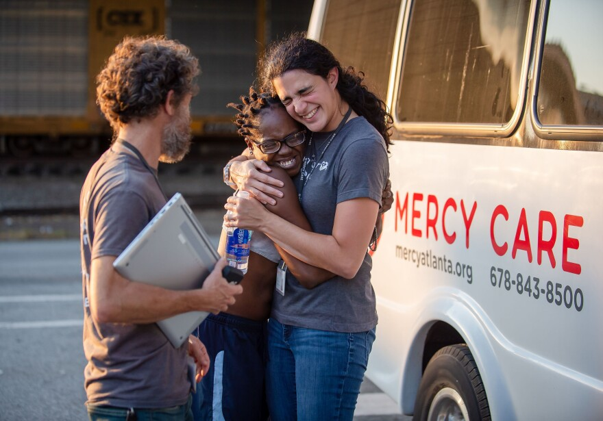 """Clinic patient Lawson (center) and nurse practitioner Fernandez de Narayan (right) share a hug outside the Mercy Care van, after the September check-in. """"We're trying to avoid emergencies, but we're also trying to build relationships,"""" says social worker Reed (left)."""