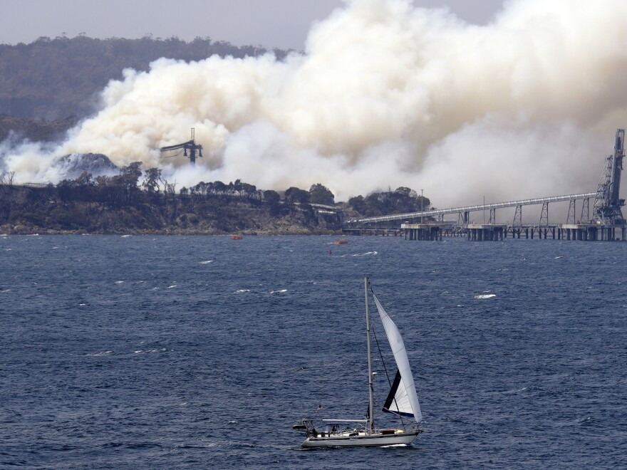 A yacht sails past a burning woodchip mill as bushfires hit the town of Eden, New South Wales, Australia, on Friday.
