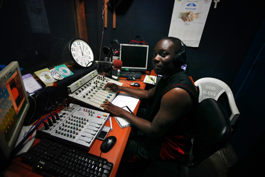 Elliott Adekoya, 31, aka The Milkman, is a DJ at Monrovia's Sky FM radio, pictured here his DJ booth. He is also part of a group of 45 Liberian musicians called the Save Liberia Project. They want to get the word out that Ebola is real, but it is <em>not </em>a death sentence. He says that message, which was propagated early on by the Ministry of Health, actually contributed to the problem.