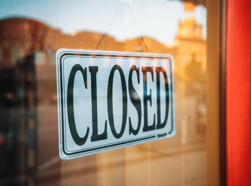 A 'Closed' sign hanging on the door of a business.