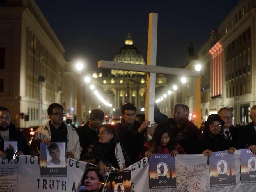 Survivors of sex abuse gather near St. Peter's Square during a twilight vigil in Rome on Thursday, the same day Pope Francis opened a landmark sex abuse prevention summit.