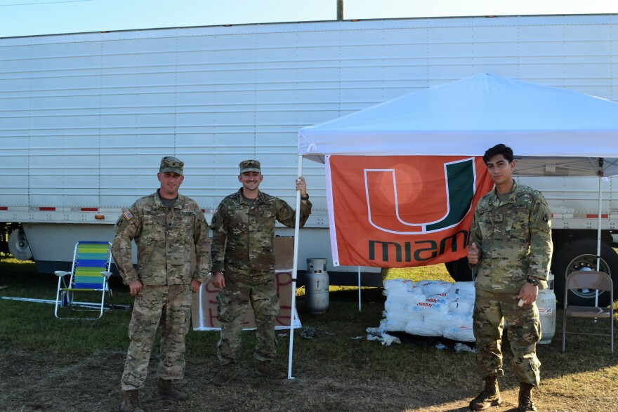 National guard membes smile near a canopy with ice. A University of Miami flag is hanging near them.